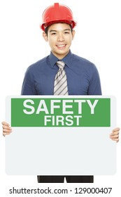 A man wearing a hardhat and holding a blank Safety First sign