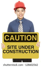 A man wearing a hardhat and holding a caution or safety sign