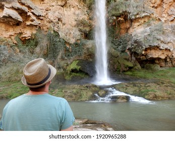 "Man wearing a hat and with his back towards the camera looking at waterfall called ""The Bride's Jump"" in Castellón (Spain)"
