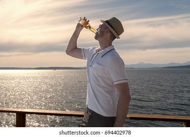 Man wearing hat on seaside deck drinking a beer close crop