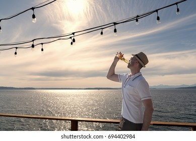 Man wearing hat on seaside deck drinking a beer under hanging lights