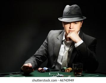 man wearing hat is playing poker in casino