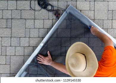 Man wearing hat replacing old material in porch door