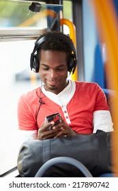 Man Wearing Headphones Listening To Music On Bus Journey