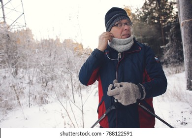 Man Wearing Headphones And Listening To Music Wearing Winter Clothes In Snowy Landscape for skiing