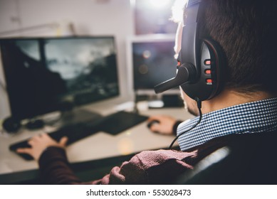 Man wearing headphones and playing video game