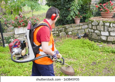 man wearing helmet and ear protectors mowing grass in the backyard with petrol hedge trimmer