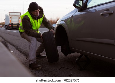 Man wearing high visibility jacket changes a wheel with flat tyre to a car stopped on a hard shoulder of a motorway