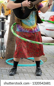 man wearing hippie style clothing playing guitar and twirling a hula hoop on street corner