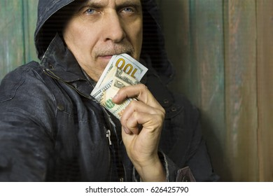 Man wearing hood holding a banknote in doubt, closeup cropped portrait