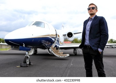 Man wearing jacket and sunglasses by the business jet aircraft
