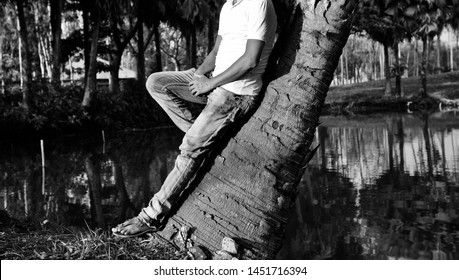 Man wearing jeans standing beside a palm tree unique photo