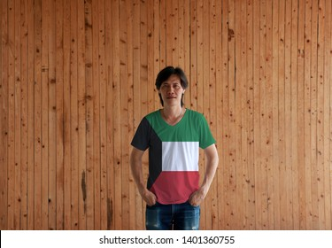 Man wearing Kuwait flag color shirt and standing with two hands in pant pockets on the wooden wall background, green white and red color with black trapezium based on the hoist side.