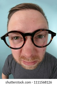 Man wearing large glasses stretching forwards to peer into the lens in a distorted perspective emphasising his eyes and glasses in a fun portrait