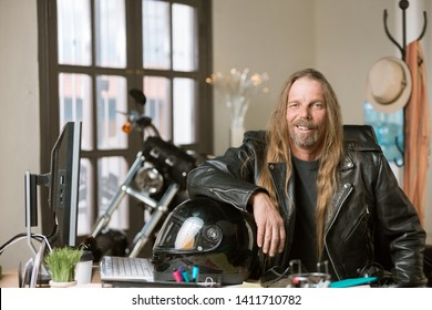 Man wearing leather jacket in his office with a motorcycle