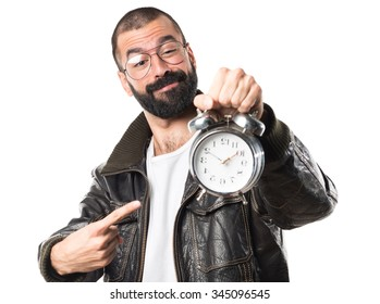Man wearing a leather jacket holding vintage clock