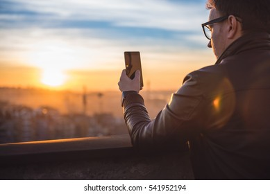Man wearing leather jacket using smart phone on the rooftop