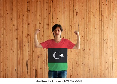 Man wearing Libya flag color of shirt and standing with raised both fist on the wooden wall background, red black and green with a white crescent and star.