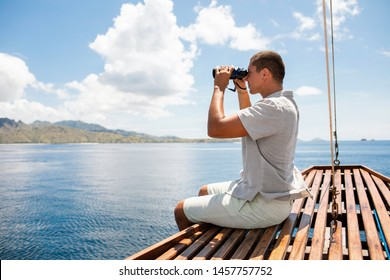 Man wearing in light linen clothes holding binoculars in hands. He looking away and sitting on marine wooden stern. Young man exploring the ocean. Background of sea and blue water.