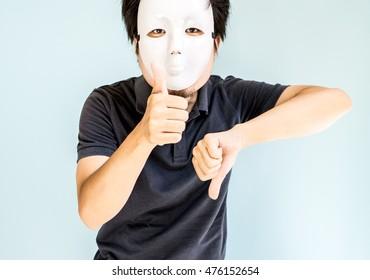 Man wearing mask making thumb-up and thumb-down