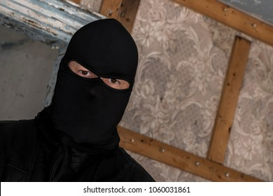 A man wearing a mask/hood in an abandoned building. He is staring at the viewer. Closeup view at an angle.