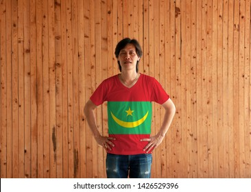 Man wearing Mauritania flag color shirt and standing with akimbo on the wooden wall background, two red stripes flanking a green field with a golden crescent and star.