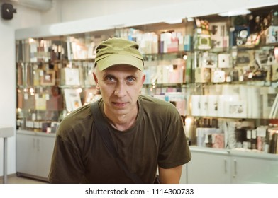 A man wearing miltary uniform posing in a shop