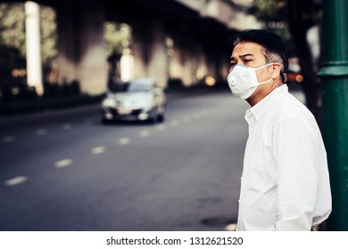 A man wearing mouth mask against air smog pollution with PM 2.5 in Bangkok city, Thailand.
