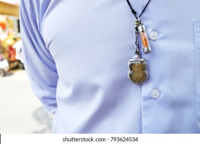 the man wearing a necklace with Thai Buddha amulet - is a kind of Thai Buddhist blessed item for luck, money, wealth, and business prosperity.