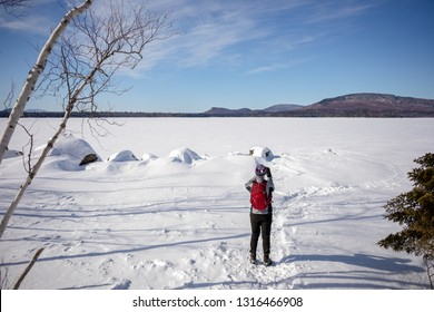 Man wearing nordic ski clothing photographing the winter view at Flagstaff Lake in western Maine.