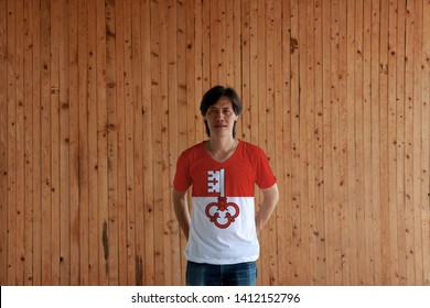 Man wearing Obwalden flag color of shirt and standing with crossed behind the back hands on the wooden wall background. The canton of Switzerland Confederation.