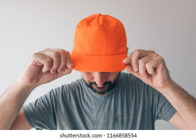 Man wearing orange baseball cap for mockup text or graphics design