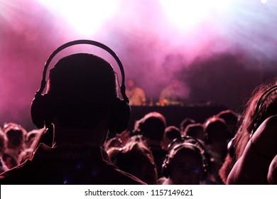 A man wearing a pair of headphones enjoying a silent disco.