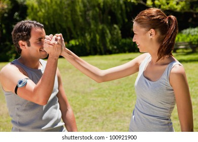Man wearing a pedometer and a woman smiling as they clasp hands with each other