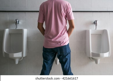man wearing a pink shirt stood pee in the restroom. Concept of urinary system problems