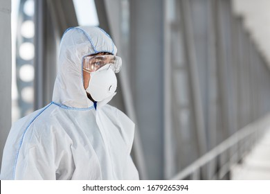 Man wearing protective biological suit and mask due to coronavirus global pandemic warning and danger.