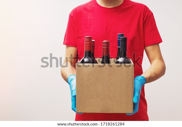 Man wearing protective gloves holding box with bottles of wine. Safe online wine store delivery during quarantine.