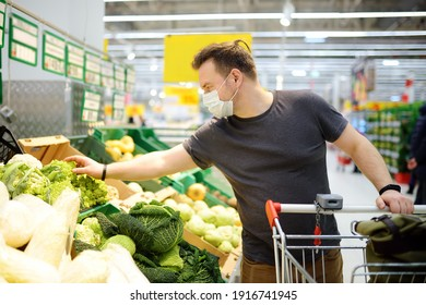 Man wearing protective medical face mask shopping in supermarket during coronavirus pneumonia outbreak. Social distancing restrictions and facemask - measures safety while covid-19 pandemic