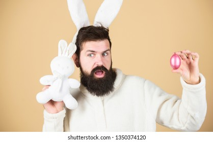 Man wearing rabbit suit. Funny bunny man soft ears. Easter activities concept. Weirdo concept. Celebrate Easter. Guy bearded hipster weird bunny with long white ears beige background. Easter rabbit.