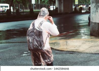 A man wearing raincoat, monsoon season, raining in Bangkok, Thailand.