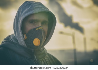 man wearing a real anti-pollution, anti-smog and viruses face mask; dense smog in air