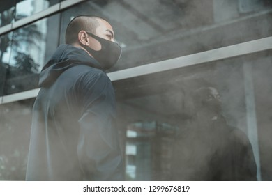 man wearing a real anti-pollution, anti-smog and viruses face mask; dense smog in air and holding big bags