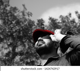 Man wearing red cap holding his sunglass and standing in a place