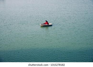 Man wearing red jacket sitting on a round shape boat around a lake