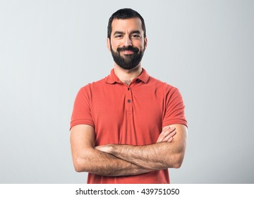 Man wearing red polo shirt with his arms crossed over grey background