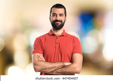 Man wearing red polo shirt with his arms crossed on unfocused background
