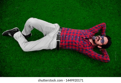 Man wearing red shirt lying on a green grassy surface