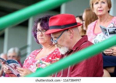 Man wearing red top and red trilby hat with goatee beard and spectacles in the crowd at Thirsk Races : Thirsk Racecourse, Thirsk, Nth Yorkshire, UK : 3 August 2018 : Pic Mick Atkins