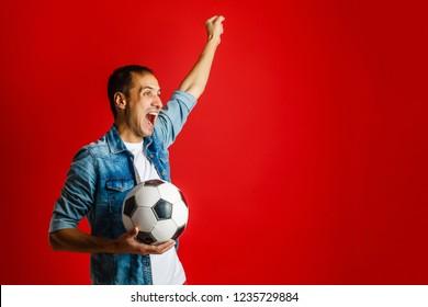 Man wearing red uniform celebrates on red background