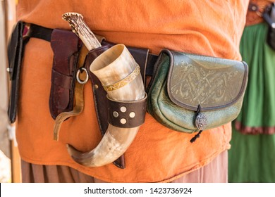 Man wearing Renaissance Fair period costume with a belt carrying knives and animal powder horn.